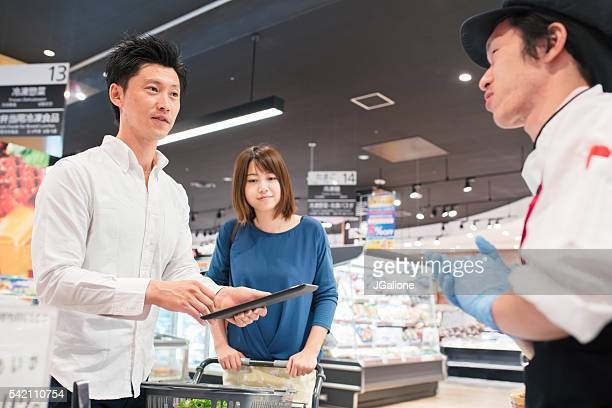 Young couple talking to staff member at a supermarket