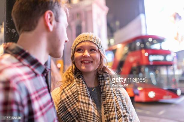 young couple talking while standing at piccadilly circus with double-decker bus in background - mode of transport stock pictures, royalty-free photos & images