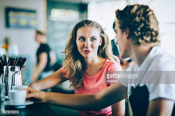 Pareja joven hablando con todas las demás en Café