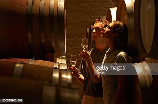 young couple tasting wine in wine cellar - 地下貯蔵室 ストックフォトと画像