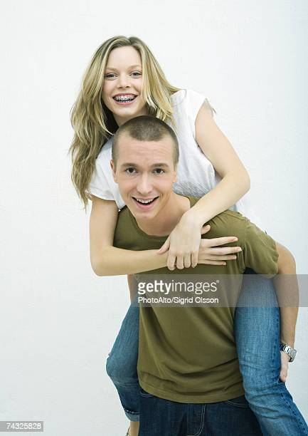 Young couple, teenage girl on young man's back, white background