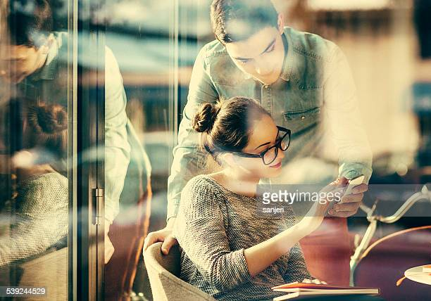Young couple text messaging at the coffee shop
