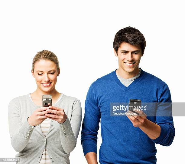 Young Couple Texting on Cellphones - Isolated