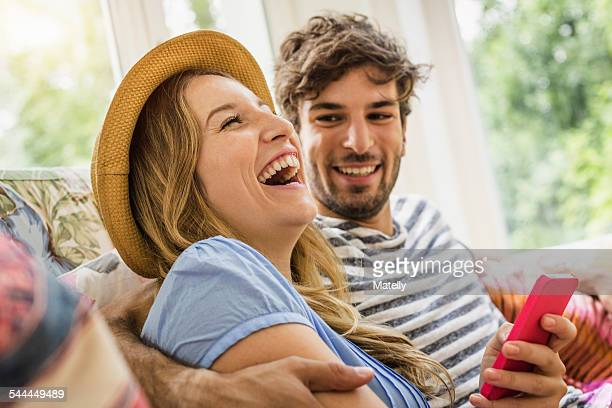 Young couple texting on smartphone in living room