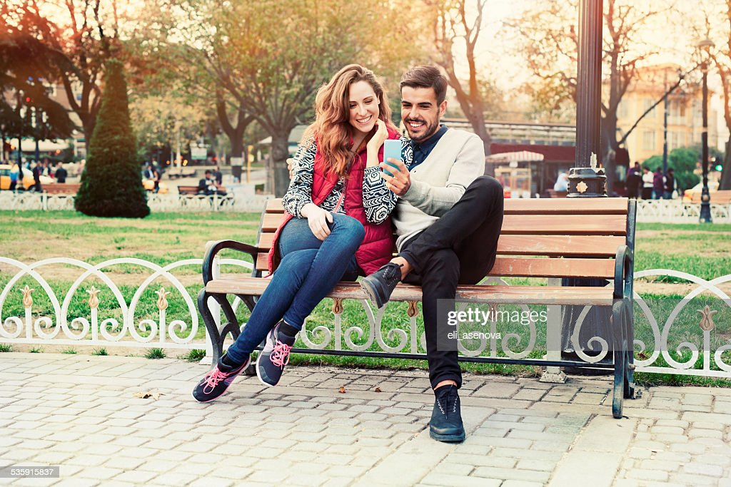 Young couple texting on smartphone : Stock Photo
