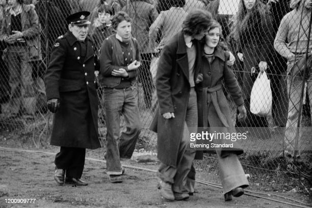 Young couple, the man with his arm around the woman, walk before a young football fan accompanied by a St John Ambulance volunteer at the FA Cup...