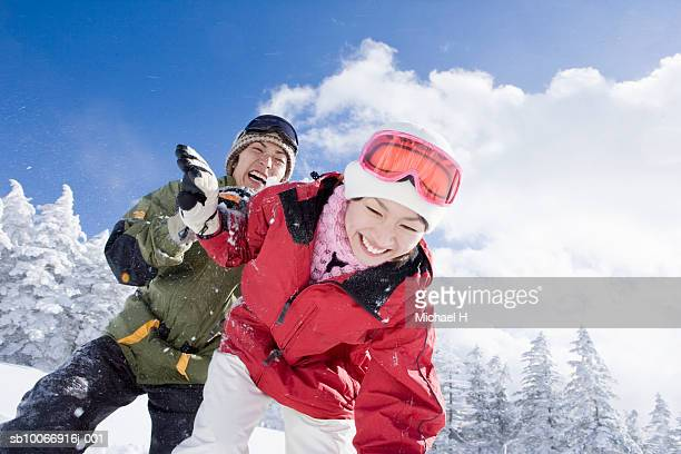 Young couple throwing snow in winter forest