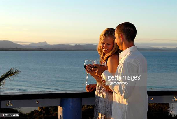 Young couple toasting at sunset on balcony by the sea