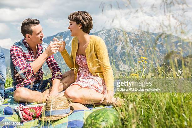 Young couple toasting each other on picnic, Tyrol, Austria