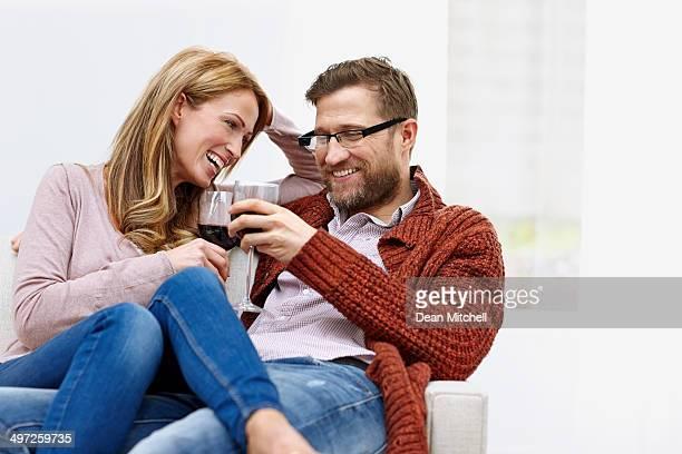 Jeune couple portant un toast de vin dans le salon