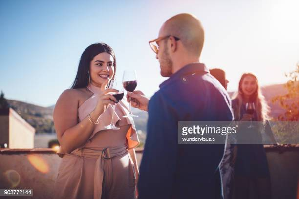 Young couple toasting with red wine at rustic cottage patio