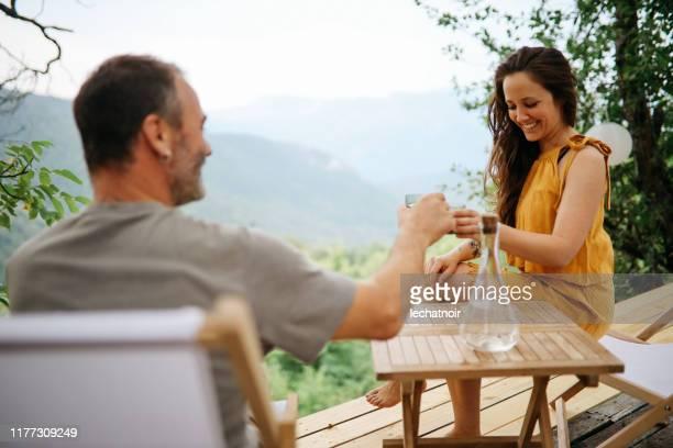 自然の中でワインで乾杯する若いカップル - ピンクの頬 ストックフォトと画像