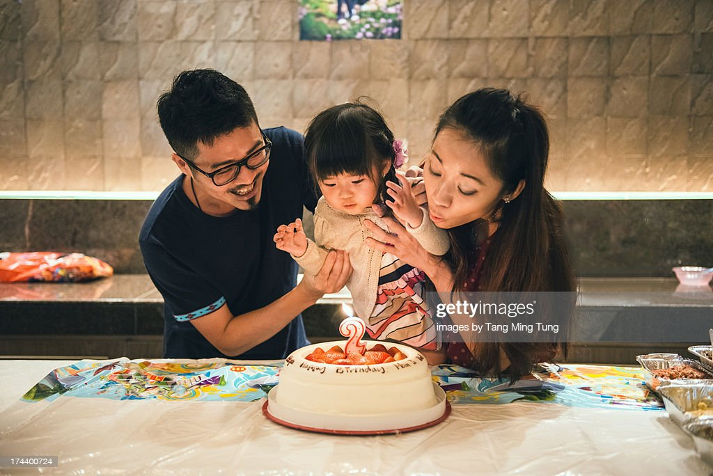 Young couple & toddler blowing birthday candle : Stock Photo