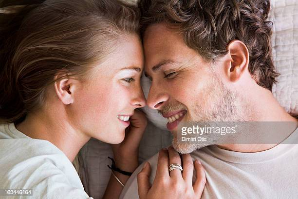 young couple touching noses in bed - verliefd worden stockfoto's en -beelden