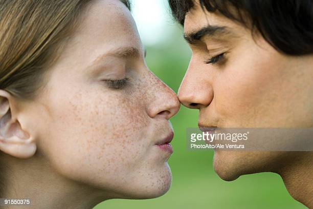 Young couple touching noses, puckering, profile