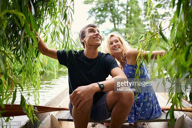 Young couple touching willow tree foliage from rowing boat on rural river