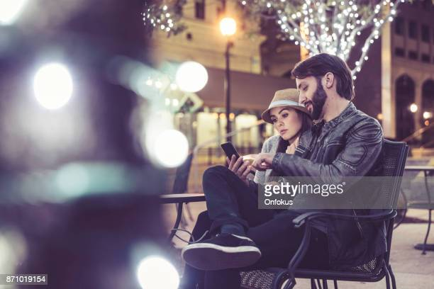 junges paar reisende sitzen am tisch im öffentlichen park in new york city - new york weihnachten stock-fotos und bilder