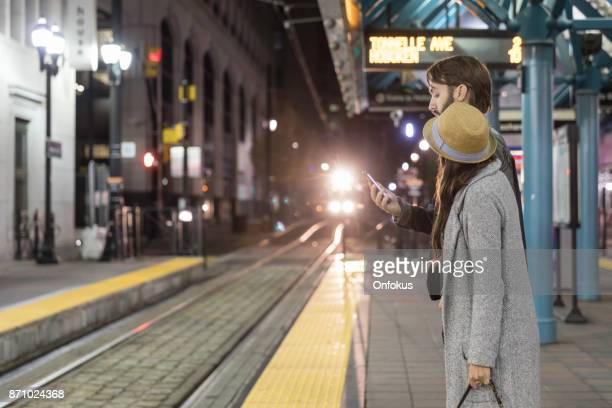 young couple travellers waiting at train bus station in new york city - new jersey stock pictures, royalty-free photos & images