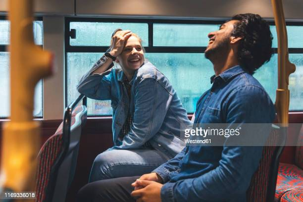 young couple travelling by bus on rainy day having fun, london, uk - heterosexual couple stock pictures, royalty-free photos & images