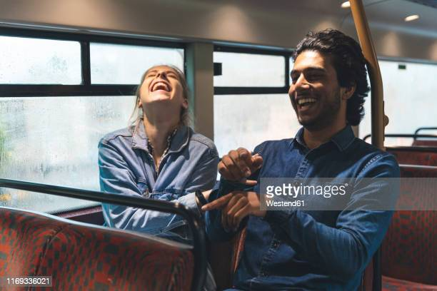 young couple travelling by bus on rainy day having fun, london, uk - humour stock pictures, royalty-free photos & images
