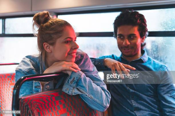 young couple travelling by bus on rainy day, london, uk - heterosexual couple stock pictures, royalty-free photos & images