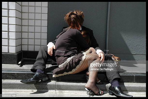 A young couple tries to recuperate on the sidewalk after a long night out without sleep