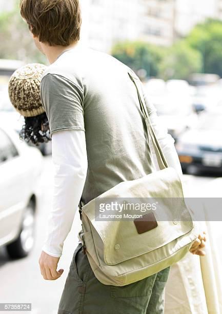 young couple trying to cross busy street - crossbody bag bildbanksfoton och bilder