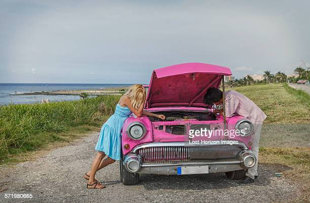 Young couple trying to fix a vintage convertible at coast, Havana, Cuba