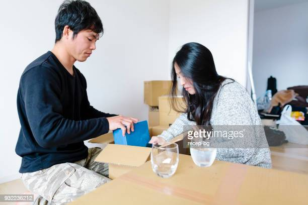 Young couple unboxing boxes in their new house