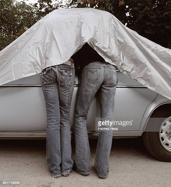 Young Couple Under Car Cover