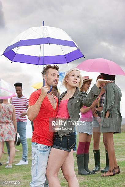 Junges Paar mit Schirm im Regen festival, Tests für