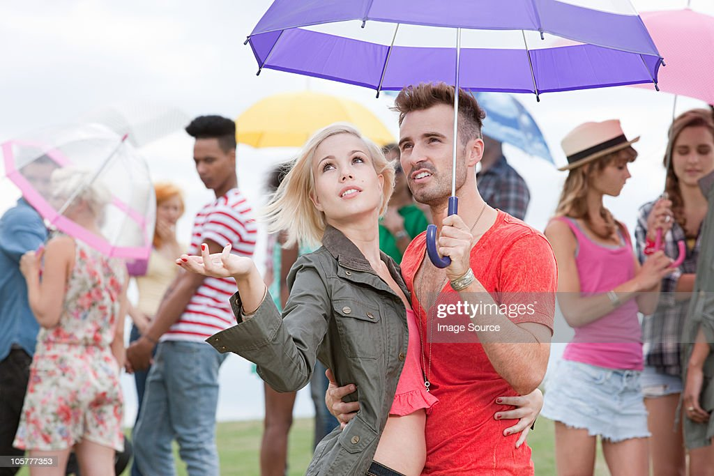 Young couple under umbrella at festival, testing for rain : Stock Photo