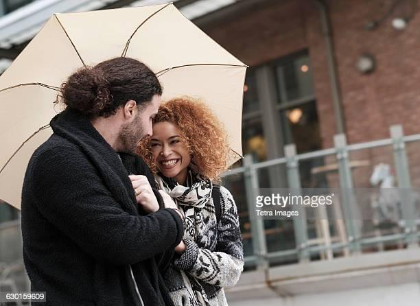 Young couple under umbrella walking through city