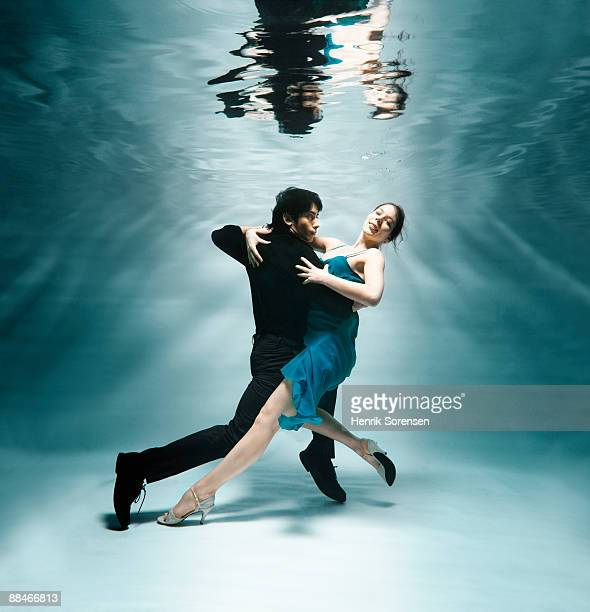 young couple under water dancing