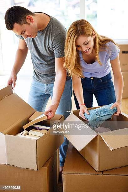 Young couple unpacking together and having fun