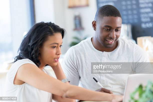 Young couple use computer in coffee shop
