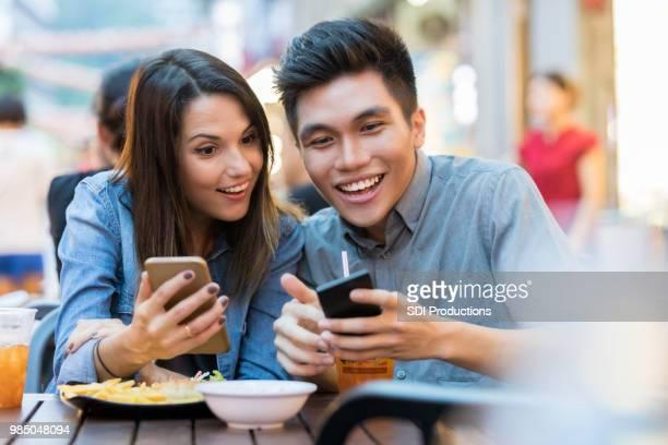 若いカップルは、ランチをしながらスマート フォンを使用してください。 - 中華街 ストックフォトと画像
