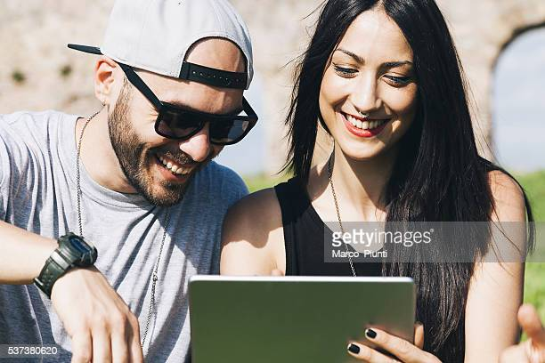 Young couple using a digital tablet at the park