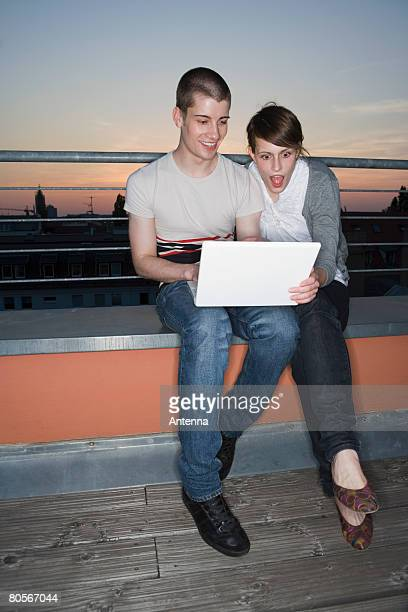 A young couple using a laptop computer on a rooftop terrace