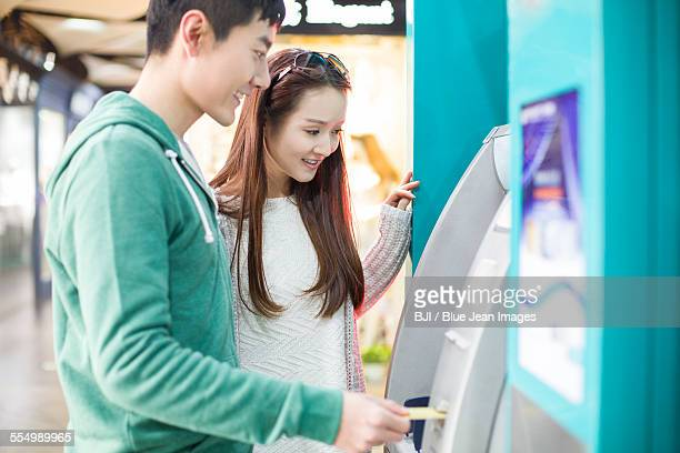 Young couple using ATM