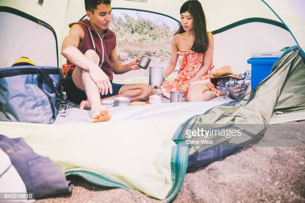 Young Couple Using Camping Equipment In Sun Shelter On The Beach