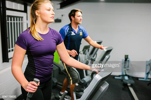 Young couple using cross trainers in the gym