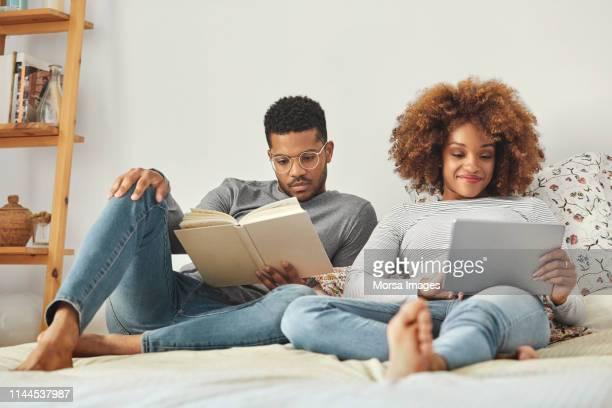 jong paar met behulp van digitale tablet en lezen boek - afro amerikaanse etniciteit stockfoto's en -beelden