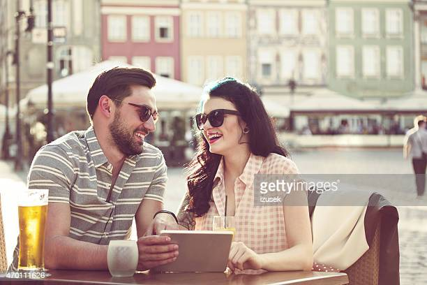 Young couple using digital tablet in the outdoor restaurant