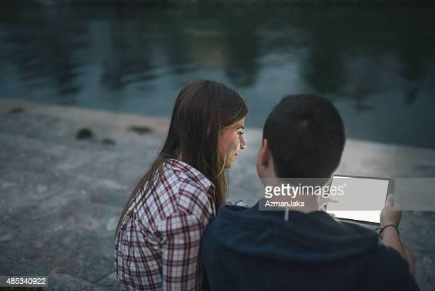 Jeune couple à l'aide de tablette numérique à l'extérieur de la ville