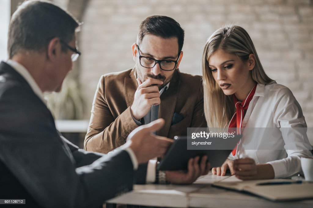 Young couple using digital tablet with their financial advisor in the office. : Stock Photo