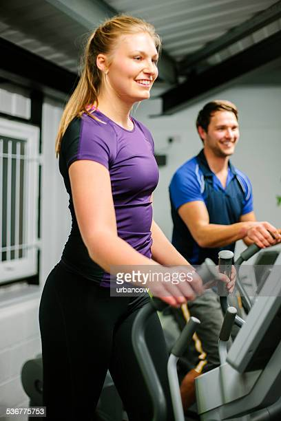 Young couple using elliptical trainers in the gym
