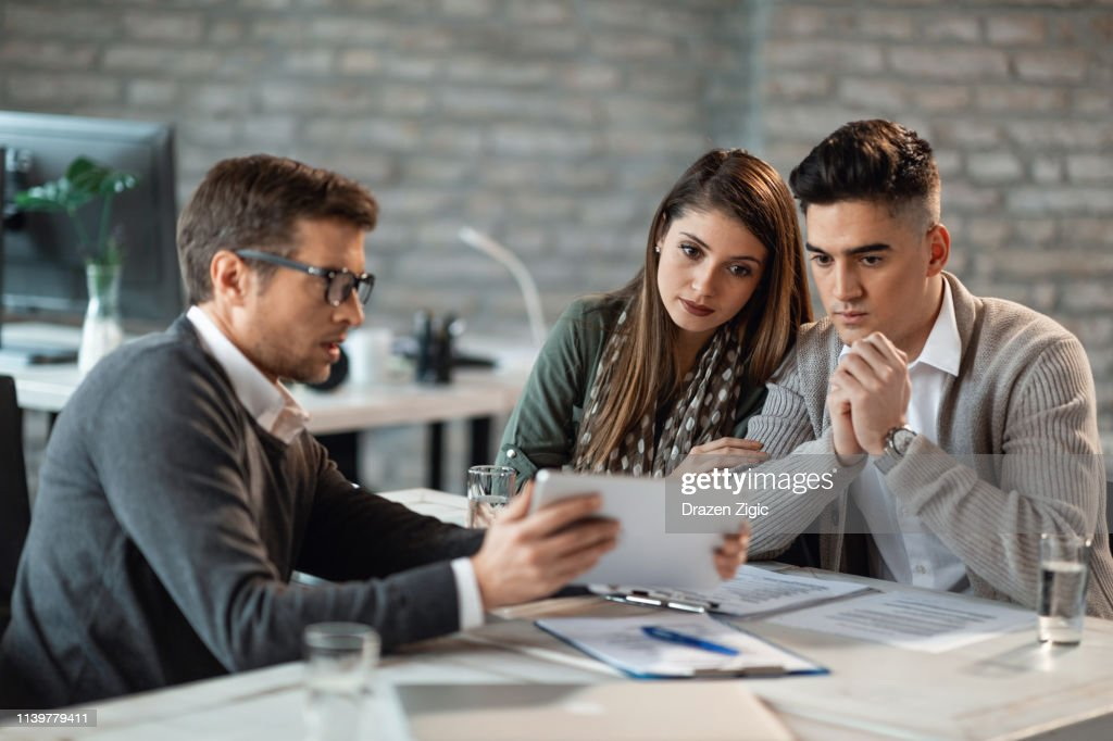 Young couple using e-reader with their insurance agent in the office. : Stock Photo