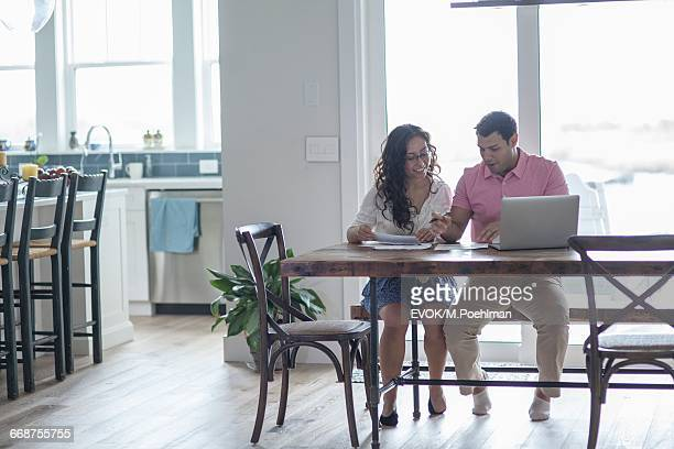 Young couple using laptop at table in living room
