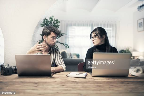 young couple using laptop computers at home - side by side stock pictures, royalty-free photos & images